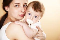Bebê com o pacifier no braço da matriz Imagens de Stock