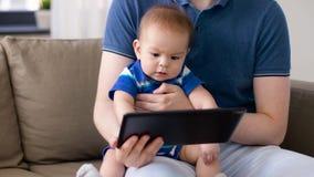 Bebê com o pai que olha o PC da tabuleta em casa filme
