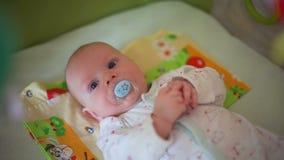 Bebê com o Soother que olha o móbil em uma ucha video estoque