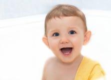 Bebê feliz com olhos azuis em uma toalha fotos de stock