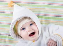 Bebê com olhos azuis grandes no chapéu e no revestimento mornos Imagens de Stock Royalty Free