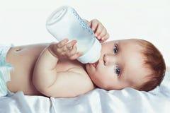 Bebê com olhos azuis que bebe de uma garrafa Fotografia de Stock