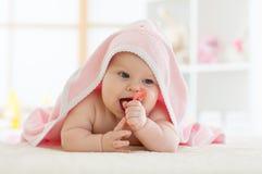 Bebê com teether na boca sob o banho da toalha no berçário foto de stock