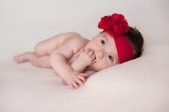 Bebê com um grande, vermelho, faixa da flor Imagens de Stock