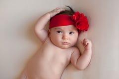 Bebê com um grande, vermelho, faixa da flor Fotografia de Stock Royalty Free