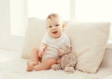 Bebê com urso de peluche em casa na sala branca Imagem de Stock