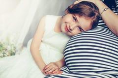 Bebê consideravelmente novo que sorri perto da mãe grávida Imagem de Stock