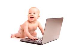 Bebê e um computador portátil isolado foto de stock