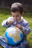 Bebê curioso com globo imagem de stock