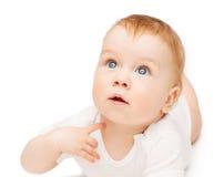 Bebê curioso que encontra-se no assoalho e que olha acima imagens de stock royalty free