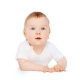 Bebê curioso que encontra-se no assoalho e que olha acima fotografia de stock royalty free