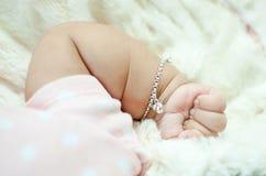 Bebê da mão que coloca na cama Foto de Stock