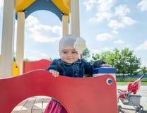 Bebê da menina no chapéu com uma flor e um revestimento azul da sarja de Nimes e um vestido vermelho que jogam no campo de jogos  Fotografia de Stock