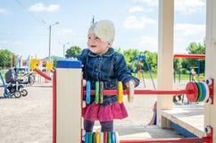 Bebê da menina no chapéu com uma flor e um revestimento azul da sarja de Nimes e um vestido vermelho que jogam no campo de jogos  Imagens de Stock