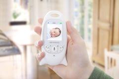 Bebê da monitoração do pai através do monitor do bebê Imagens de Stock