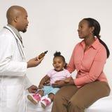 Bebê da terra arrendada da matriz que fala ao pediatra. Imagens de Stock Royalty Free