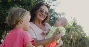 Bebê da terra arrendada da mulher adulta perto de pouca criança filme