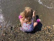 Bebê da vista superior que senta-se na praia, sentando e jogando a areia na praia imagem de stock
