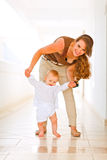 Bebê de ajuda da mamã feliz a andar Fotos de Stock