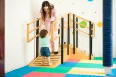 Bebê de ajuda do terapeuta a andar fotos de stock royalty free