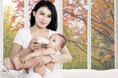 Bebê de alimentação da mãe com garrafa de leite Foto de Stock Royalty Free