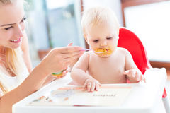 Bebê de alimentação da matriz com colher Fotografia de Stock