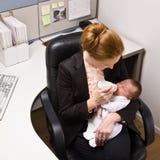 Bebê de alimentação da mulher de negócios na mesa Fotos de Stock Royalty Free