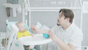 Bebê de alimentação do pai que senta-se na cadeira alta em casa filme