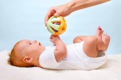 Bebê de colocação pequeno com brinquedo Fotos de Stock Royalty Free