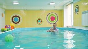 Bebê de ensino a nadar na piscina filme