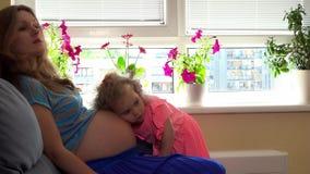 Bebê de escuta da barriga da mãe da mulher gravida da menina bonito da filha da criança para dentro filme