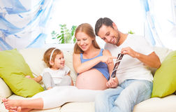 Bebê de espera da família feliz que olha a mamã grávida do ultrassom, d Fotos de Stock Royalty Free