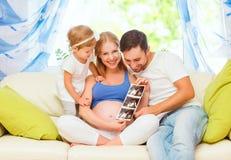 Bebê de espera da família feliz que olha a mamã grávida do ultrassom, d Fotografia de Stock