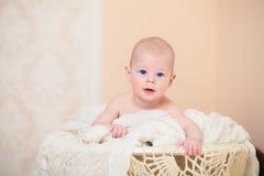 Bebê de olhos azuis bonito que encontra-se na barriga Imagem de Stock