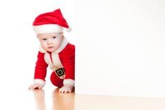 Bebê de Papai Noel que olha atrás do cartaz Fotografia de Stock