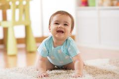 Bebê de rastejamento em casa no assoalho Imagem de Stock Royalty Free