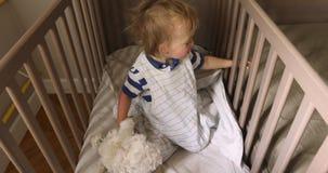 Bebê de riso bonito que senta-se na cama após o tempo da sesta filme
