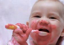 Bebê de riso com uma colher na boca Fotos de Stock