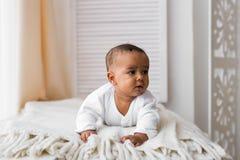 Bebê de riso da raça misturada que encontra-se na barriga em casa Foto de Stock Royalty Free