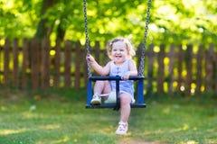 Bebê de riso no passeio do balanço no playgrond fotografia de stock royalty free