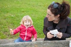 Bebê de riso que come o pão com a mulher no parque Imagens de Stock Royalty Free