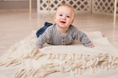 Bebê de riso que encontra-se na barriga em casa Imagens de Stock