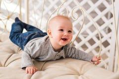 Bebê de riso que encontra-se na barriga em casa Imagem de Stock