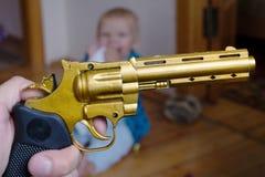 Bebê de sono com uma arma em suas mãos Imagens de Stock Royalty Free