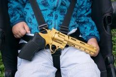 Bebê de sono com uma arma em suas mãos Foto de Stock