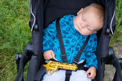 Bebê de sono com uma arma em suas mãos Fotos de Stock Royalty Free