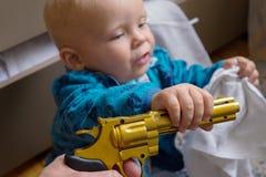 Bebê de sono com uma arma em suas mãos Fotografia de Stock Royalty Free