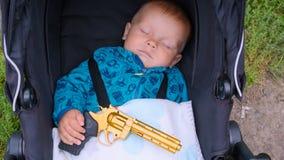 Bebê de sono com uma arma em suas mãos Fotografia de Stock