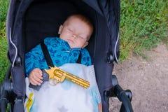Bebê de sono com uma arma em suas mãos Fotos de Stock