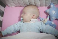 Bebê de sono de quatro meses que encontra-se no berço imagens de stock royalty free